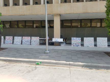 Doyle's colorful posters can be seen resting against the building as her protest against her injustice continues.
